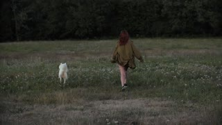 Woman Playing with Her Dog on Green Grass