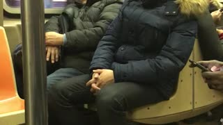 Man in blue jacket leaning on subway seat