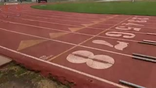 Girl trips on orange track hurdle