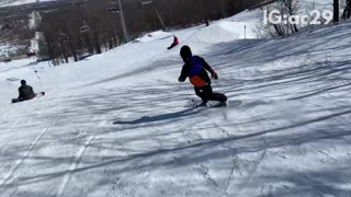 Snowboarder rides off small ramp and falls down on his butt