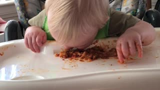 cute baby makes a mess while eating  - Video