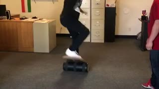 Black hat guy on balance board in office falls on shoulder