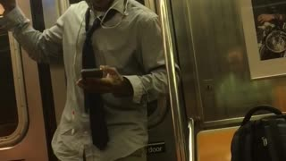 A man in a collard shirt and glasses dances on a subway train  - Video
