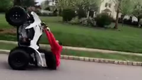 Guy red sweater jacket tries to do wheelie on atv falls on butt