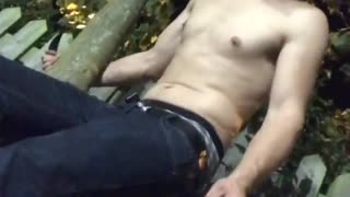 Shirtless guy cigarette sitting on wooden post breaks and lands in sitting position