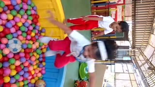 Slowmo red pants girl jumps into ball pit boy falls off - Video