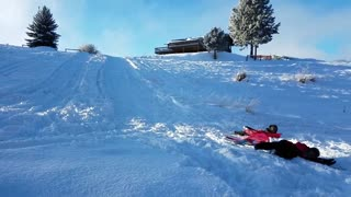 Kid red jacket sleds into other kid - Video