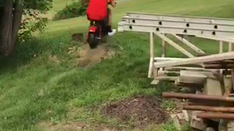 Man in red rides mini bike and falls off