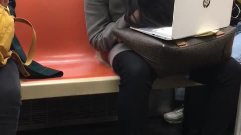 Woman slouches her head and falls asleep on a subway train with her laptop on her lap