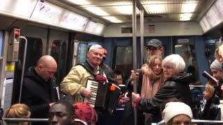 Old man playing accordion on crowded train - Video