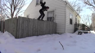 Guy flipping into snow from house - Video