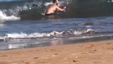 Man trying to take photo in water at beach gets knocked over by wave