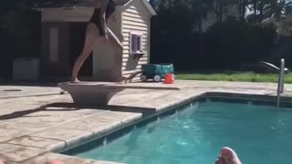Girl in black bathing suit belly flop into pool