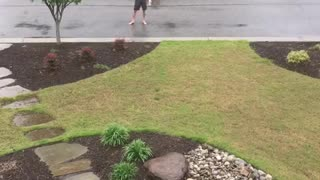 Shirtless guy showers in rain in middle of street - Video