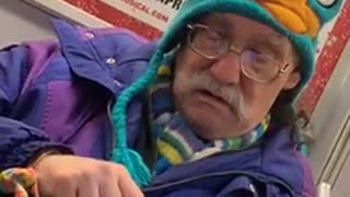 Old man wears perry the platypus beanie and bright purple jacket on subway train
