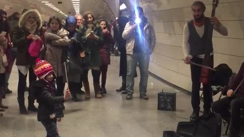 Adorable Maestro Orchestrates Performers In Subway Station