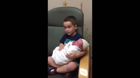 Older Brother's Hilarious Reaction To Holding Newborn Sibling For The First Time