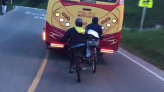 Kids on bikes hitch ride from back of bus - Video