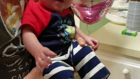 Baby giggles when sister hits a balloon