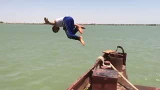 A boy jump in water in style in slow motion  - Video