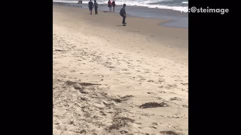 Guy riding uniboard hoverboard beach riding dirty