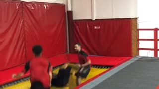 Woman bounces off of trampoline with two friends and face plants into the floor