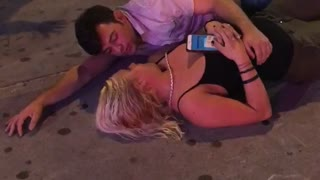 Guy laying on sidewalk with girl outside club - Video