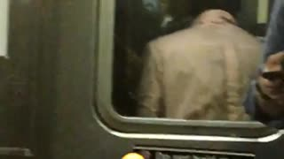 A man in a pink shirt dancing in between subway cars - Video