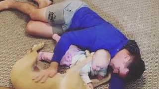 Dad, dog & baby preciously cuddle together
