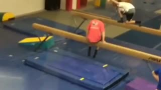 Red shirt kid hops on balance beam and falls backwards