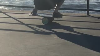 Man balancing on cylinder on pier looking at ocean