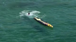 Guy yellow surfboard paddle white shirt falls into water ocean