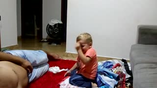 Little kid jumps off couch lands in pile of t-shirts