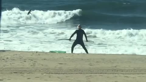 Guy with paddleboard does stretches at the beach with his paddle