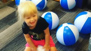 Adorable young girl play with soft balls