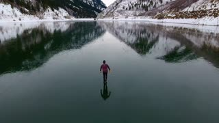 Stunning drone footage of man skating on perfectly frozen lake