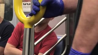 Person on subway with purple gloves holding onto pole - Video