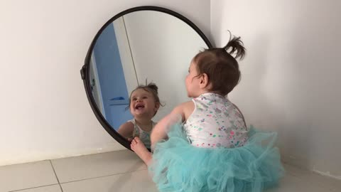 Baby plays with her reflection in the mirror
