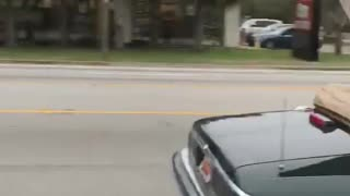 Black topless car drives down highway with unsecured wood board - Video