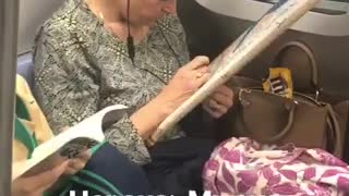 Woman cross stitching on subway train holds frame with a string tied to her ear