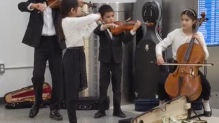 Talented Young Orchestra Playing in Lobby