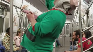 Green shirt elf jollycat sings on subway - Video