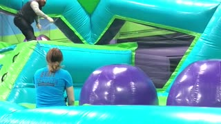 Grown man trampoline obstacle course slips on purple ball - Video