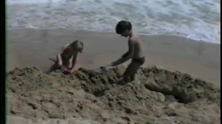 Kid's Sand Castle Becomes A Moat After Surprise Wave