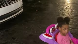 Adorable Toddler wants to park her toy car in her mum's garage