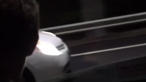 A guy drops his phone outside a car