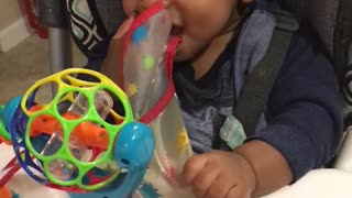Baby desperately pulls on his bib to take it off  - Video