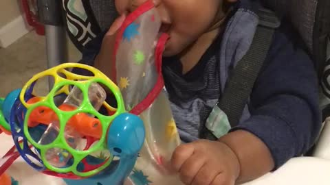 Baby desperately pulls on his bib to take it off