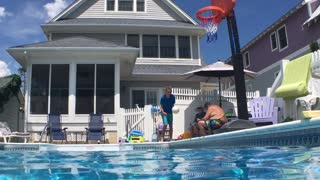 Talented kid scores a perfect slam dunk while jumping into pool - Video