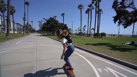 Girl skateboards with Pomeranian in her backpack